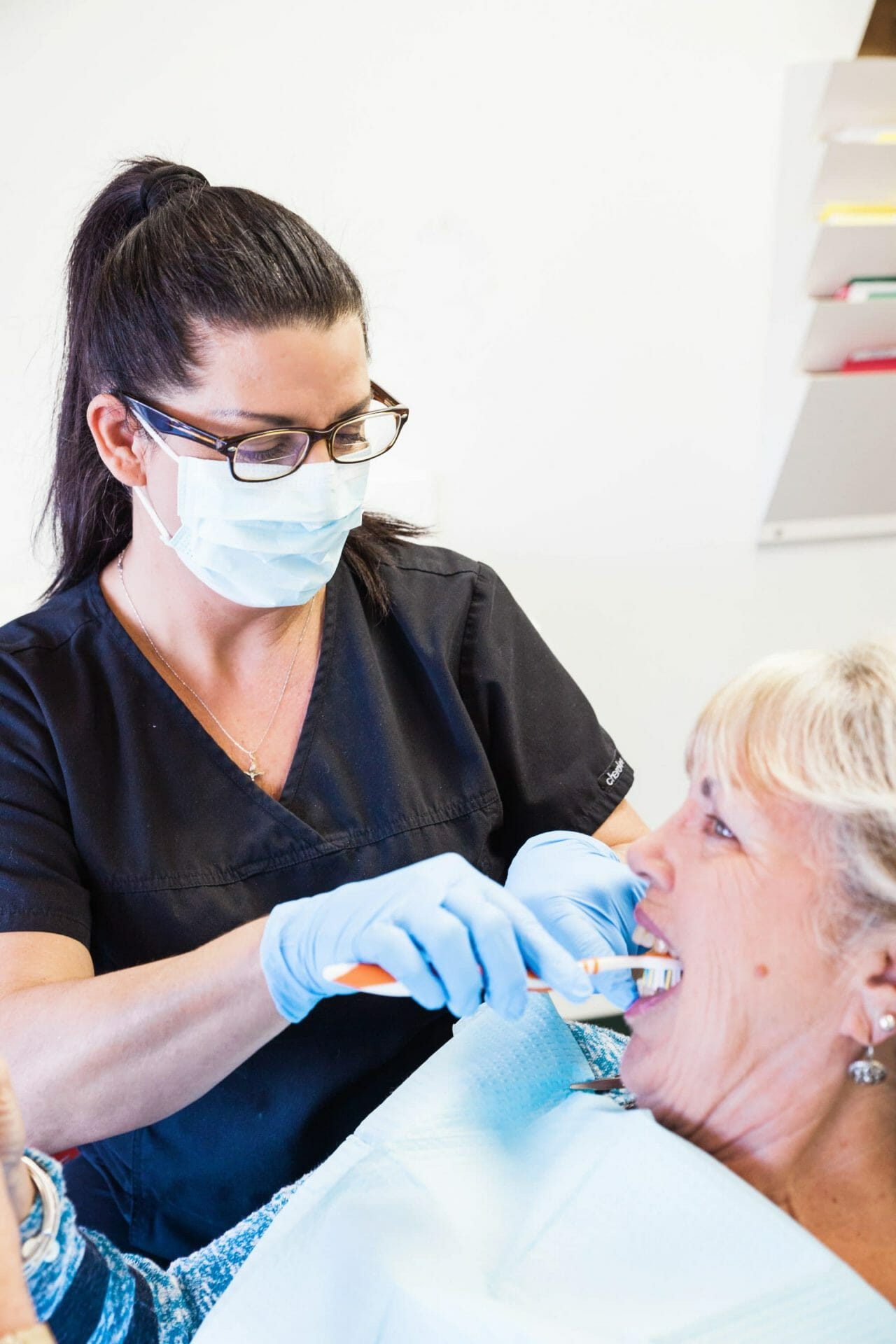 hygienist brushing patient's teeth
