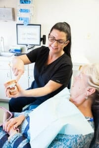 Hygienist showing a patient model teeth